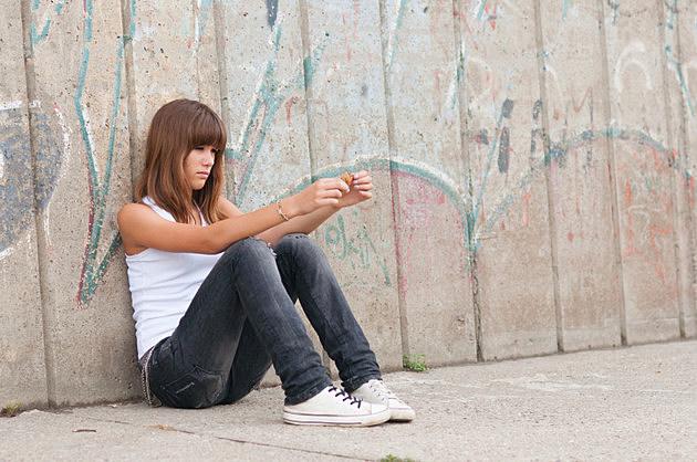 Cute sad teenage girl sitting alone