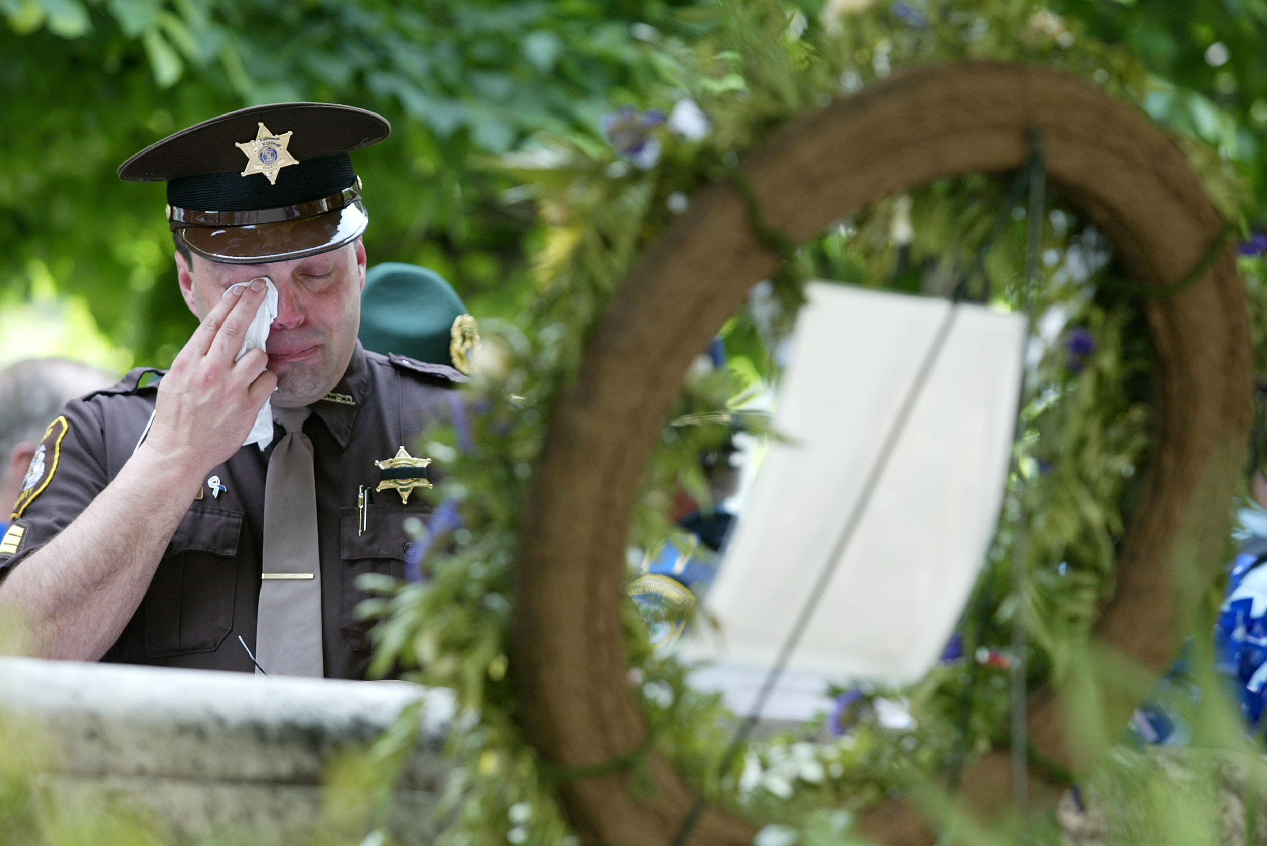 Sergeant Tony Grahovac of the sheriff department of Munising, Michigan, wipes his eyes as he moums the loss of his brother who was killed while investigating a muti-car accident, May 13, 2002 prior to the annual candlelight vigil at the National Law Enforcement Officers Memorial in Washington, DC. Thousands gather on the site of the National Law Enforcement Officers Memorial during Police Week each year to salute all of America's law enforcement heroes.